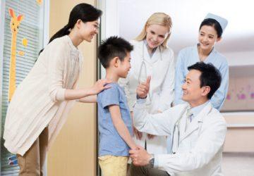 Doctor talking to little boy in hospital